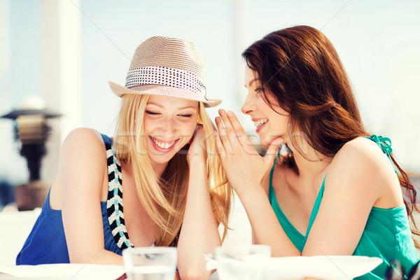 girls gossiping in cafe on the beach Stock photo © dolgachov