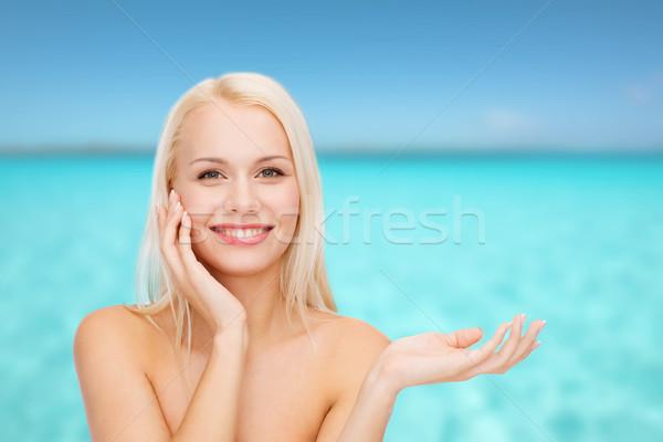 smiling woman holding imaginary lotion jar Stock photo © dolgachov