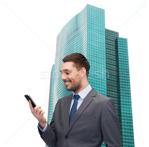 Fiatal mosolyog üzletember okostelefon üzlet technológia Stock fotó © dolgachov
