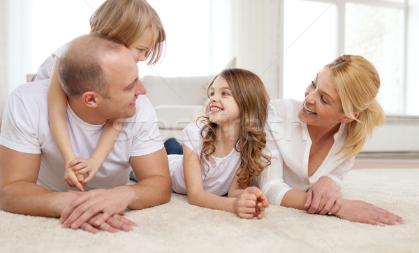 parents and two girls lying on floor at home Stock photo © dolgachov