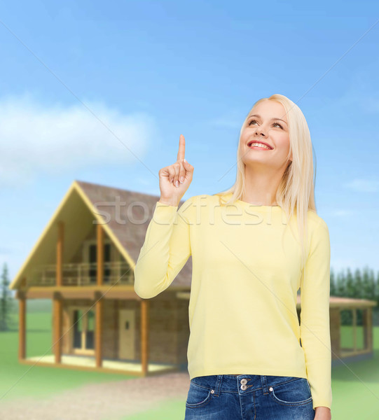 улыбающаяся женщина указывая пальца вверх реклама привлекательный Сток-фото © dolgachov