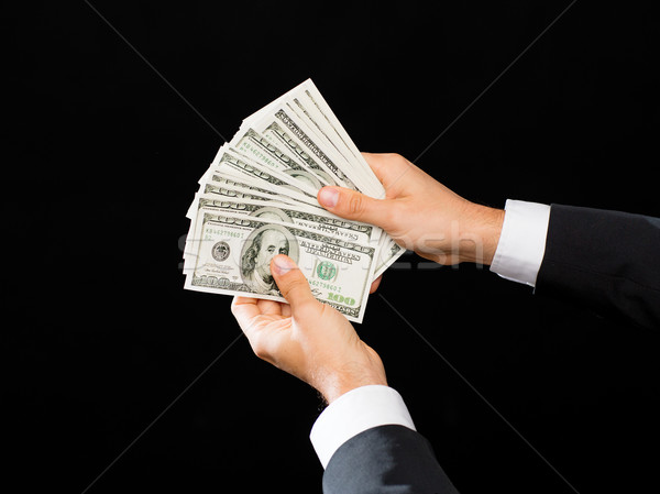 Stock photo: close up of male hands holding dollar cash money