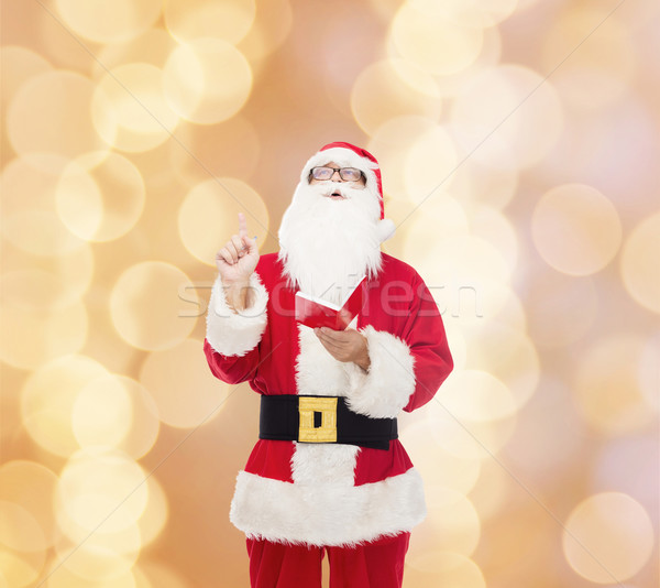 man in costume of santa claus with notepad Stock photo © dolgachov