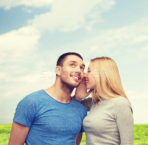 smiling girlfriend telling boyfriend secret Stock photo © dolgachov