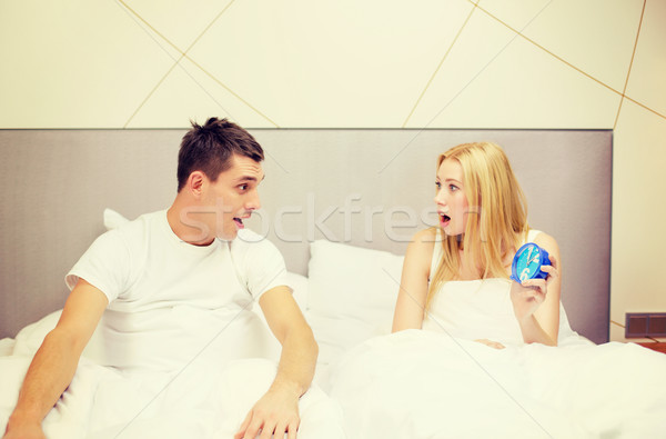 surprised couple with clock in bed Stock photo © dolgachov