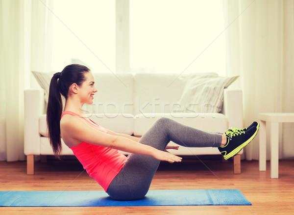 smiling girl doing exercise on floor at home Stock photo © dolgachov