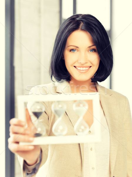 businesswoman holding hourglass Stock photo © dolgachov
