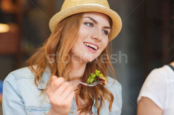happy young woman eating salad at bar or pub Stock photo © dolgachov