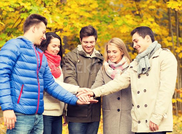 group of smiling men and women in autumn park Stock photo © dolgachov