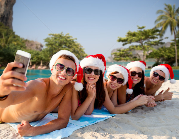 Stock photo: group of friends in santa hats with smartphone
