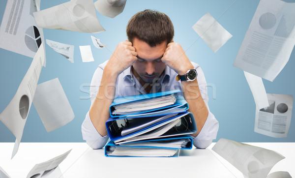 sad businessman with stack of folders at office Stock photo © dolgachov