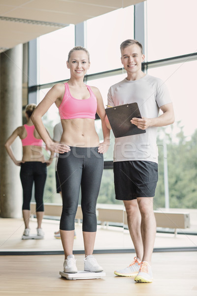 smiling man and woman with scales in gym Stock photo © dolgachov