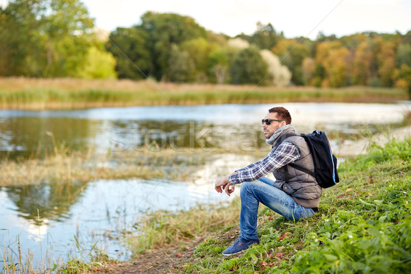 man with backpack resting on river bank Stock photo © dolgachov