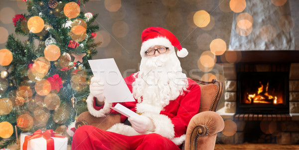 santa claus reading letter in armchair at home Stock photo © dolgachov