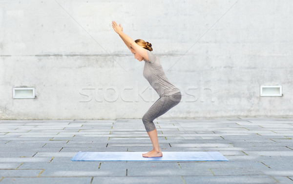 woman making yoga in chair pose on mat outdoors Stock photo © dolgachov