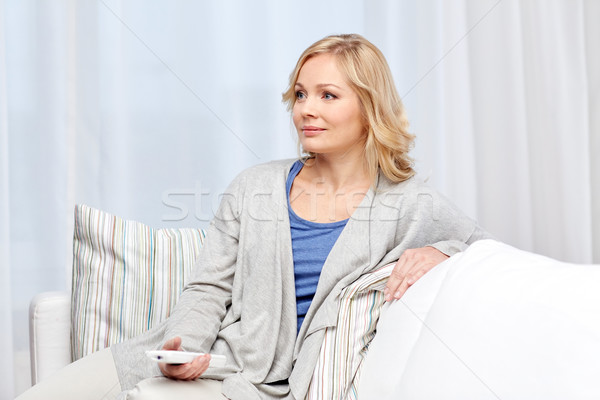 smiling woman with tv remote control at home Stock photo © dolgachov