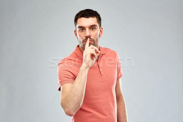young man making hush sign over gray background Stock photo © dolgachov