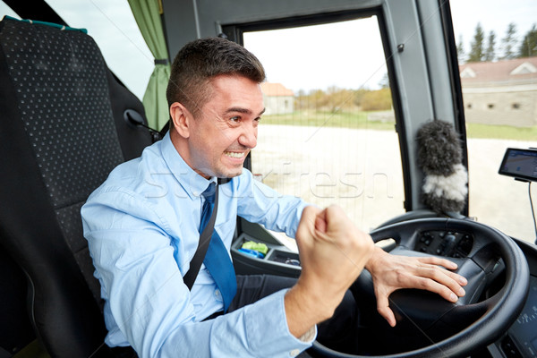 angry driver showing fist and driving bus Stock photo © dolgachov