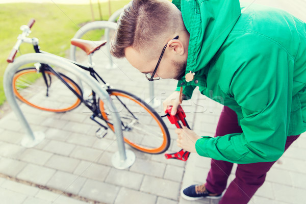 hipster man fastening fixed gear bike with lock Stock photo © dolgachov