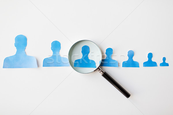 close up of paper human shapes on white board Stock photo © dolgachov