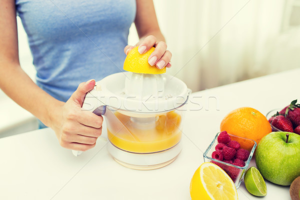 close up of woman squeezing fruit juice at home Stock photo © dolgachov