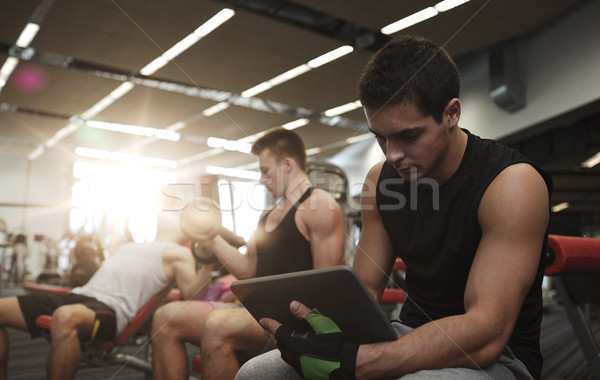 group of men with tablet pc and dumbbells in gym Stock photo © dolgachov