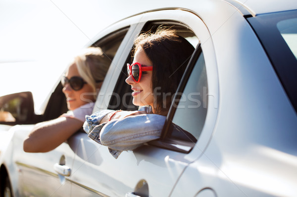 happy teenage girls or women in car at seaside Stock photo © dolgachov