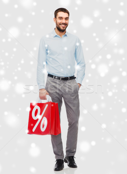 smiling man with red shopping bag over snow Stock photo © dolgachov