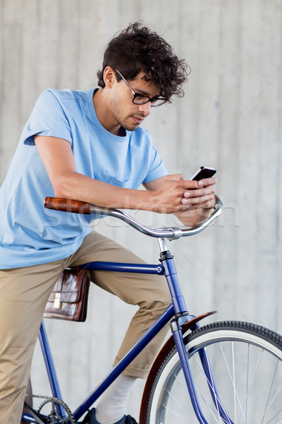 man with smartphone and fixed gear bike on street Stock photo © dolgachov