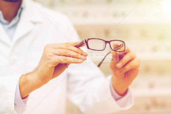 close up of optician with glasses at optics store Stock photo © dolgachov