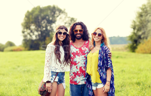 smiling young hippie friends on green field Stock photo © dolgachov