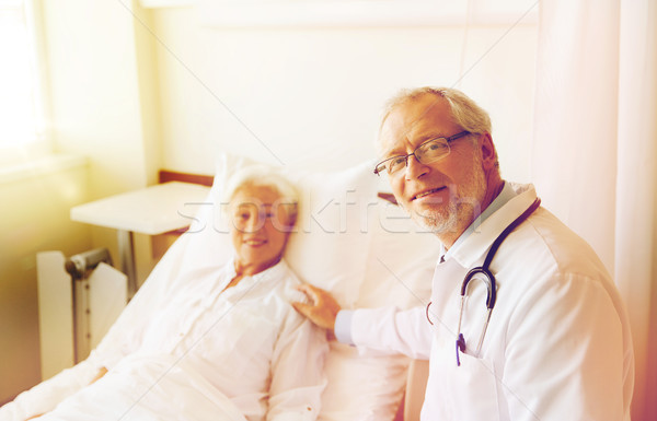 doctor visiting senior woman at hospital ward Stock photo © dolgachov
