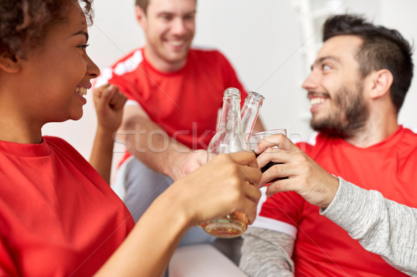 happy football fans or friends with beer at home Stock photo © dolgachov