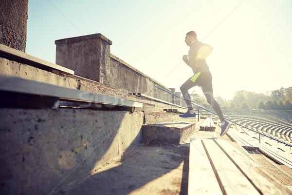 Stock photo: happy young man running upstairs on stadium
