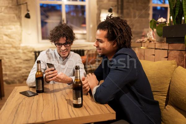 men with smartphones drinking beer at bar or pub Stock photo © dolgachov