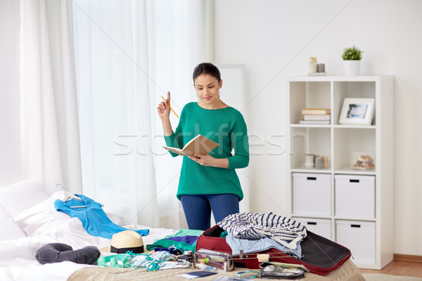 woman with notebook planning her trip at home Stock photo © dolgachov