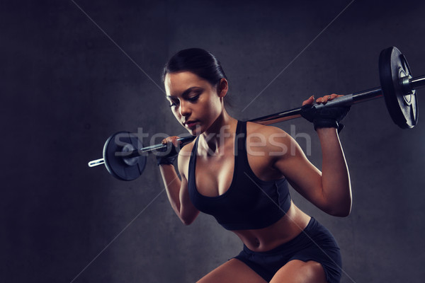 Jeune femme muscles barbell gymnase sport fitness Photo stock © dolgachov