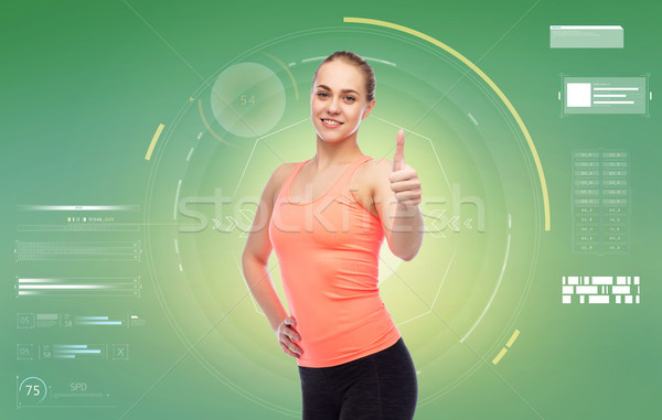 happy sportive young woman showing thumbs up Stock photo © dolgachov