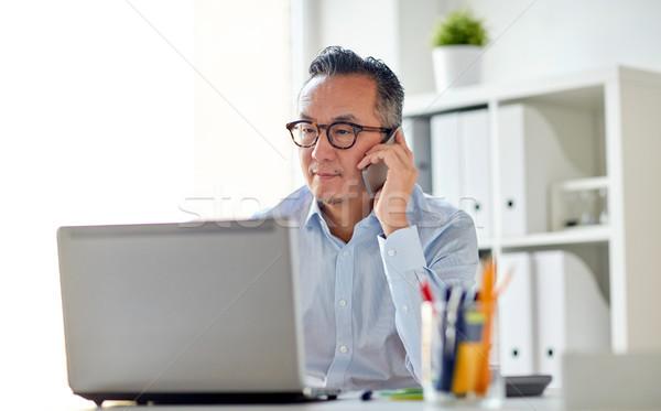 businessman with laptop calling on smartphone Stock photo © dolgachov