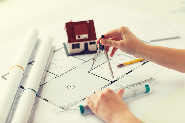 close up of hands with compass measuring blueprint Stock photo © dolgachov