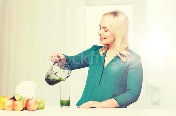 happy woman with blender jug pouring juice at home Stock photo © dolgachov