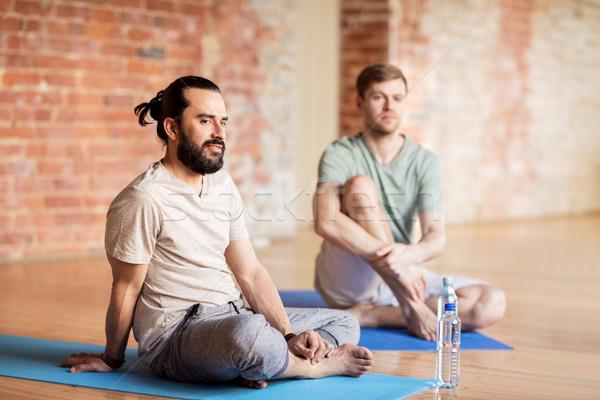 men resting on mats at yoga studio Stock photo © dolgachov