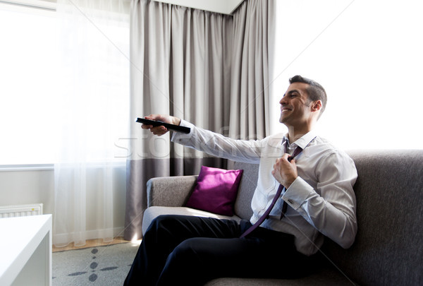 happy businessman with tv remote at hotel room Stock photo © dolgachov