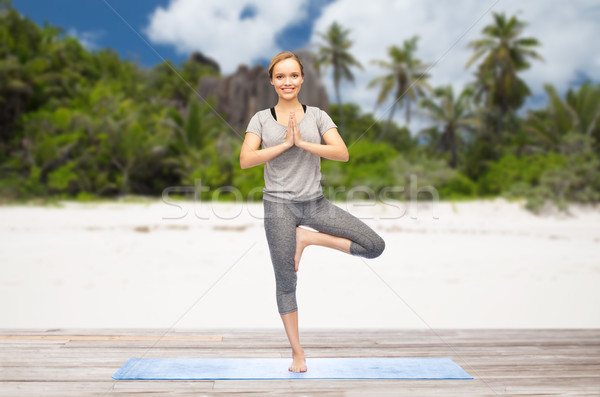 woman doing yoga in tree pose outdoors on beach Stock photo © dolgachov