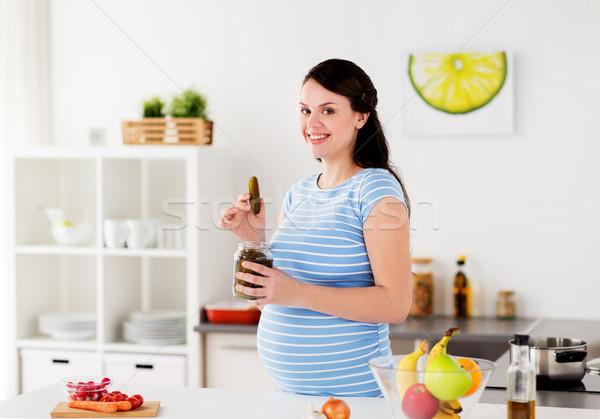 Kobieta w ciąży jedzenie ogórki konserwowe domu kuchnia ciąży Zdjęcia stock © dolgachov