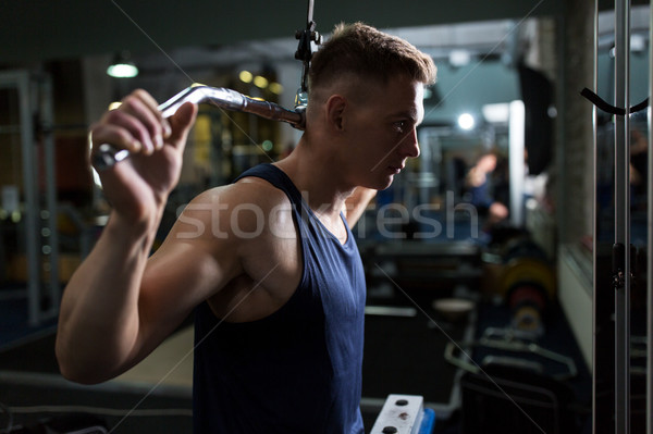 man flexing muscles on cable machine in gym Stock photo © dolgachov