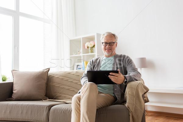 senior man with tablet pc sitting on sofa at home Stock photo © dolgachov
