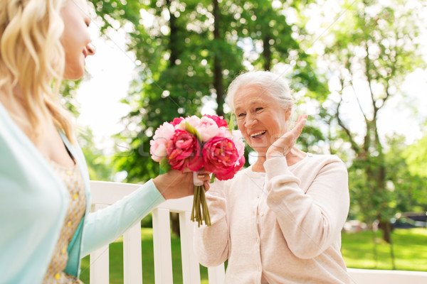Stock photo: daughter giving flowers to senior mother at park
