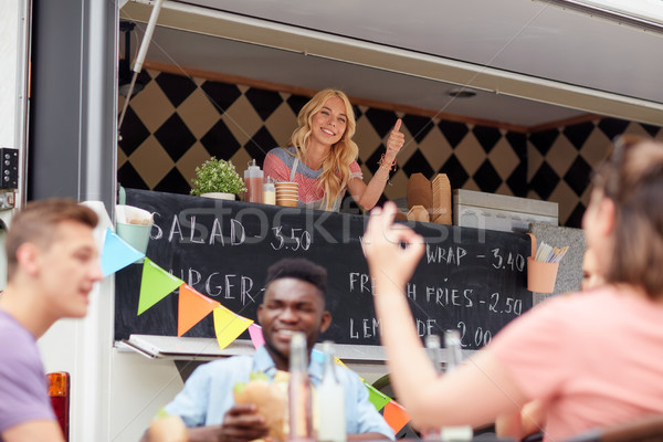 happy saleswoman showing thumbs up at food truck Stock photo © dolgachov