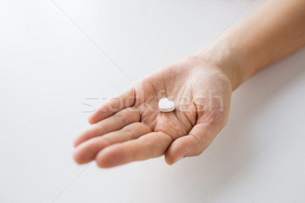 close up of hand holding medicine heart pill Stock photo © dolgachov